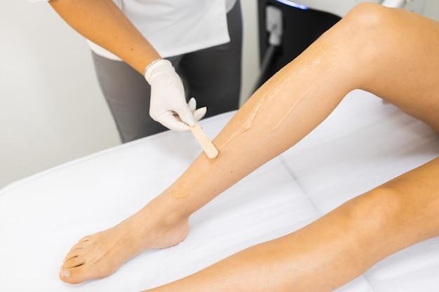 Косметолог наносит на ногу женщины специальный гель для лазерной эпиляции.