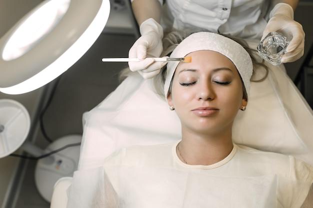 Косметолог наносит косметический продукт на пациентку с помощью кисти