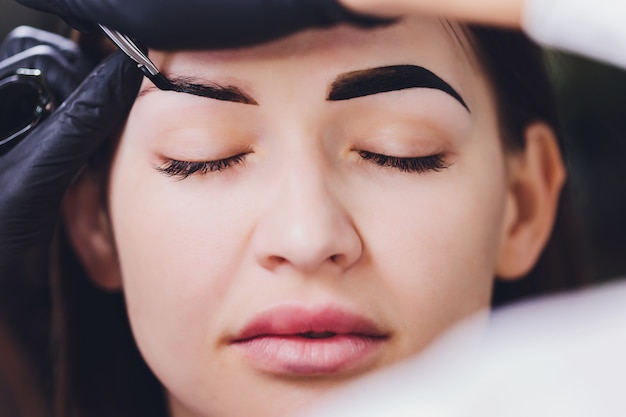 Beautician applies henna paint on trimmed eyebrows in a beauty salon