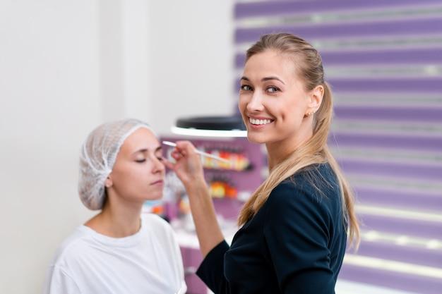 Beautician applies marking on eyebrows.
