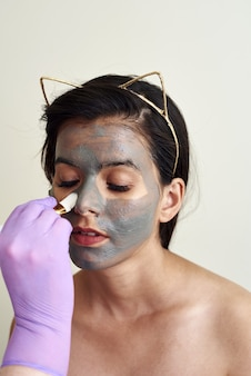 Beautician applies a moisturizing mask to the client's face.