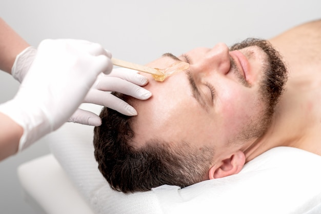 Beautician applies wax between male eyebrows before the procedure of waxing in the beauty salon