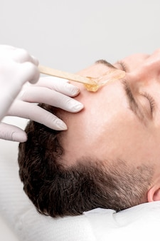 Beautician applies wax between male eyebrows before the procedure of waxing in the beauty salon.
