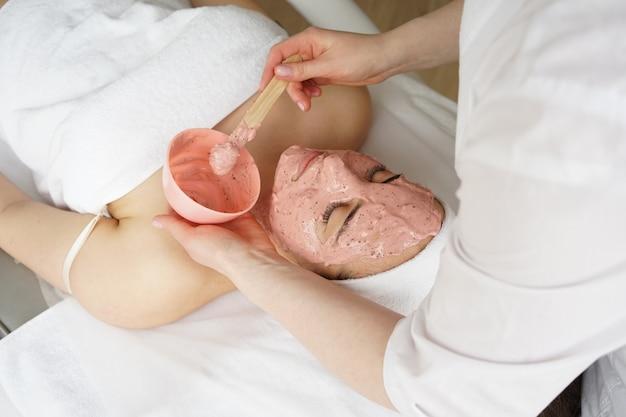 美容師は彼女の患者にアルギン酸マスクを適用します