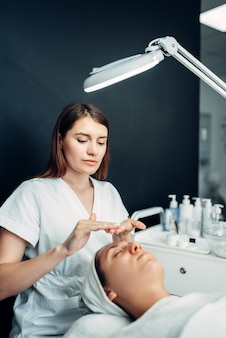 Косметолог наносит крем-маску на лицо пациента.