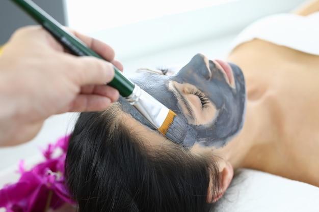 Косметолог, применяя маску из черной глины к женщине с кистью