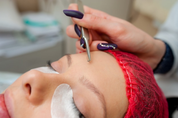 Beautician applying eyelash extensions
