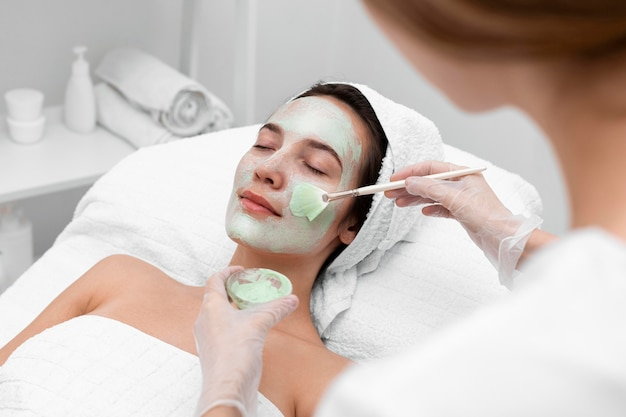 Beautician applying face mask on female client