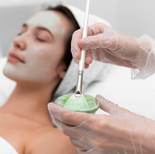 女性のクライアントにフェイスマスクを適用する美容師