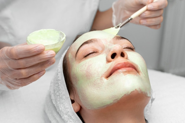 여성 고객에 얼굴 마스크를 적용하는 미용사