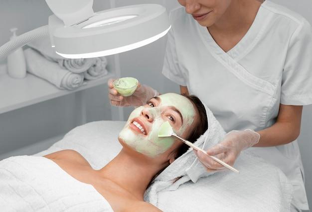 Косметолог, применяя маску для лица на клиентке