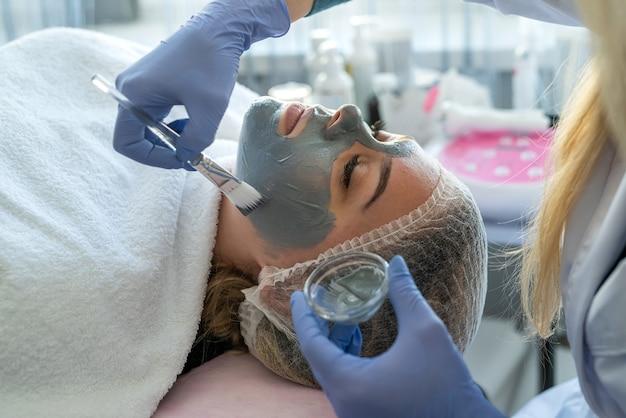 スパサロンで女性クライアントにフェイシャルマスクを適用する美容師。健康管理