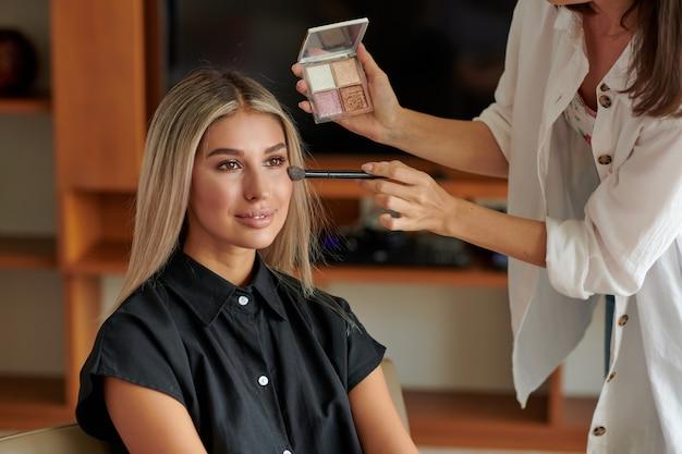 Косметолог наносит макияж на клиента