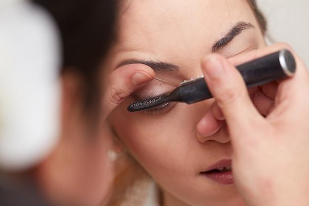 Beautician applying make up