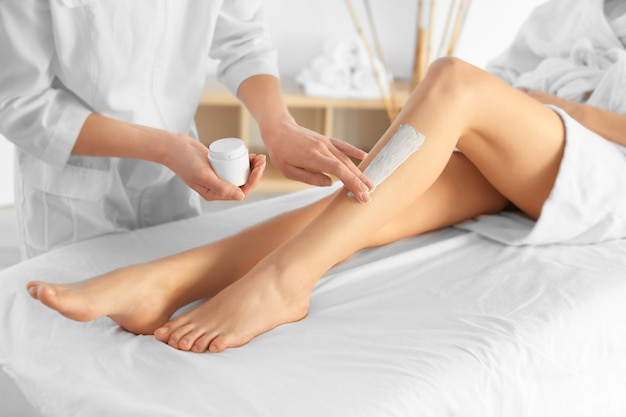 Beautician applying moisturizing cream on female legs in spa center