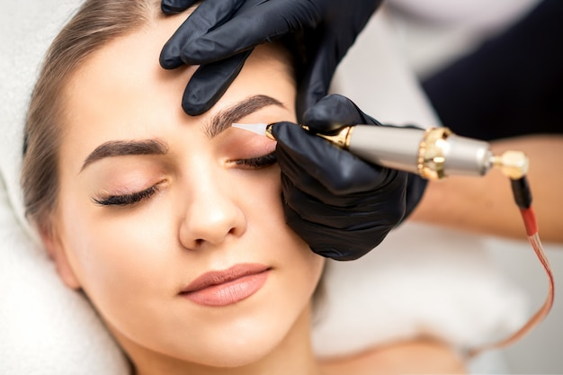 Beautician applying permanent makeup on eyebrows by tattoo machine tool
