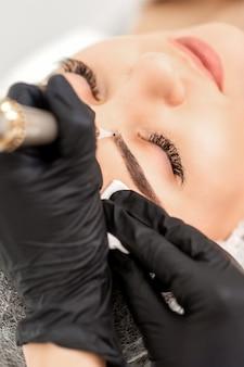 Косметолог, наносящий перманентный макияж на брови тату-станком
