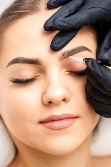 Косметолог наносит перманентный макияж на брови молодой женщины специальным тату-станком