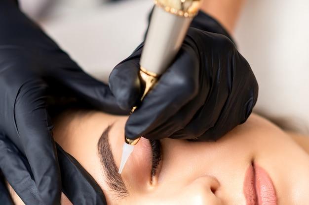 Косметолог наносит перманентный макияж на брови молодой женщины на специальном тату-станке