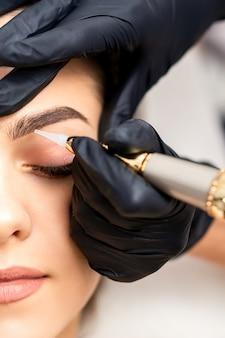 Косметолог, применяя перманентный макияж на бровях молодой женщины