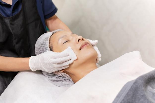 美容師は概念的な綿パッドスキンケアスパで女性の顔を掃除します。