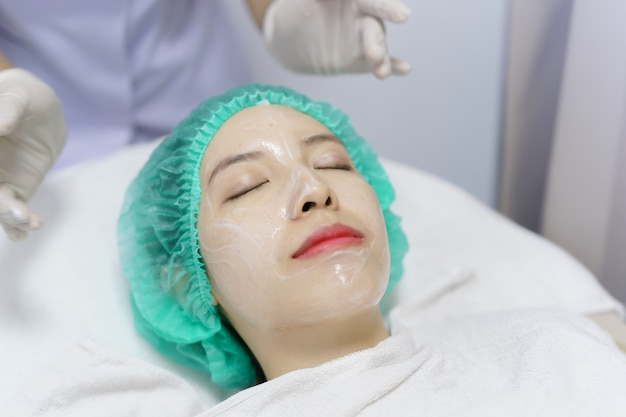 Beautician cleansing facial woman in beauty salon, spa.