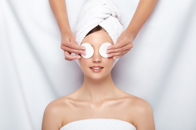Beautician closing woman's eyes with two cotton pads