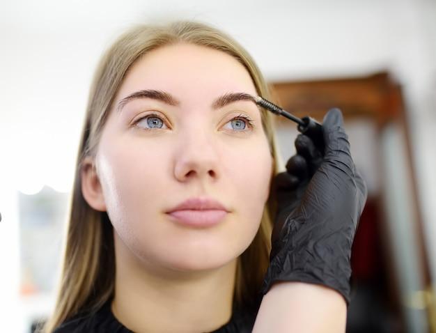 美容師は、顔の若い美しいモデルに特別なブラシを使用して眉毛をとかします。フェイシャルケアとメイクアップ
