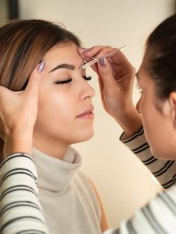 美容師がピンセットで若い女性の眉毛を矯正