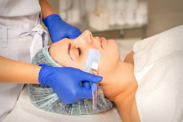 スパビューティーサロンでのスキンケア中に、女性の顔の皮膚を保湿クレンジングマスクで覆う美容師。