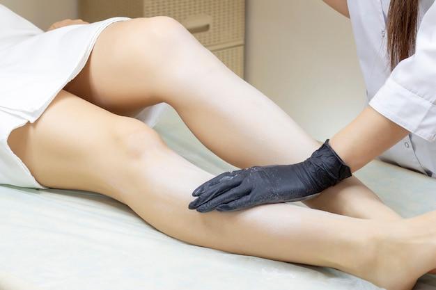 美容師がウェルネスセンターで液体の砂糖で女性の足を脱毛