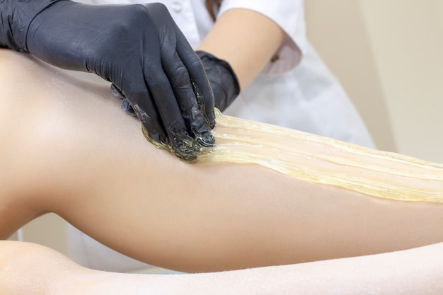 Beautician depilating woman's legs with liquid sugar in spa center