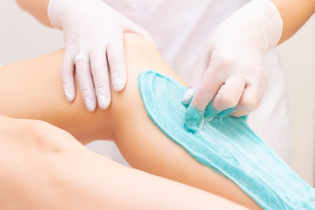 Beautician depilating young womans legs with liquid sugar in spa center. depilation of legs with turquoise sugaring paste