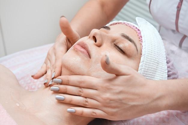 美容師の医者は若い女性の肌をきれいに
