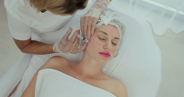 미용사는 젊은 아름다운 여성의 얼굴 피부에 주사를 합니다. 미용실에서 얼굴 메조테라피 절차. 메조테라피, 바이오리바이탈라이제이션. 미용술.