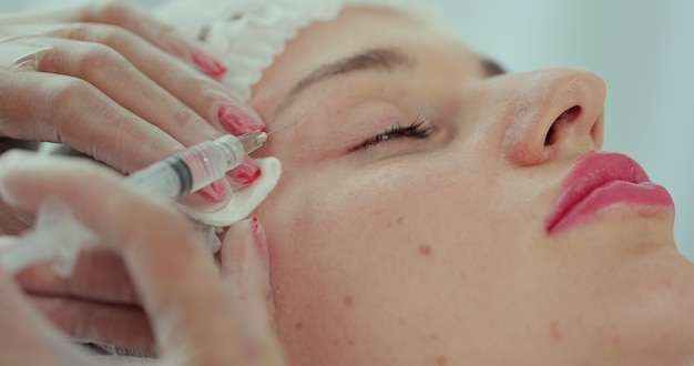미용사는 젊은 아름다운 여성의 얼굴 피부에 주사를 합니다. 미용실에서 얼굴 메조테라피 절차. 메조테라피, 바이오리바이탈라이제이션.