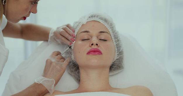 미용사는 젊은 아름다운 여성의 얼굴 피부에 주사를 합니다. 혈소판이 풍부한 플라즈마 얼굴 주사 절차의 상위 뷰 클로즈업 샷.