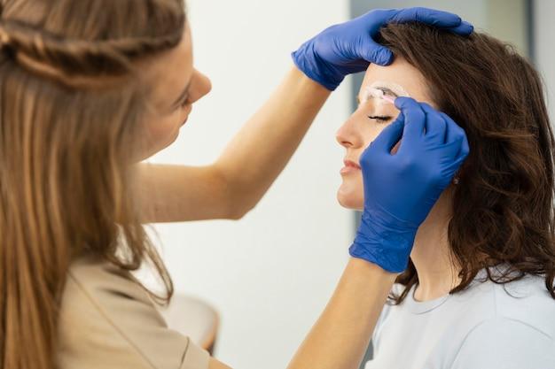 그녀의 여성 고객을 위해 눈썹 치료를하는 미용사