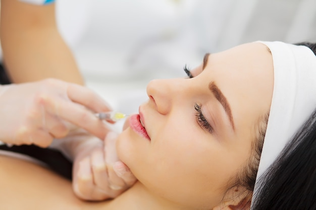 Beautician doing beauty injection to woman lips