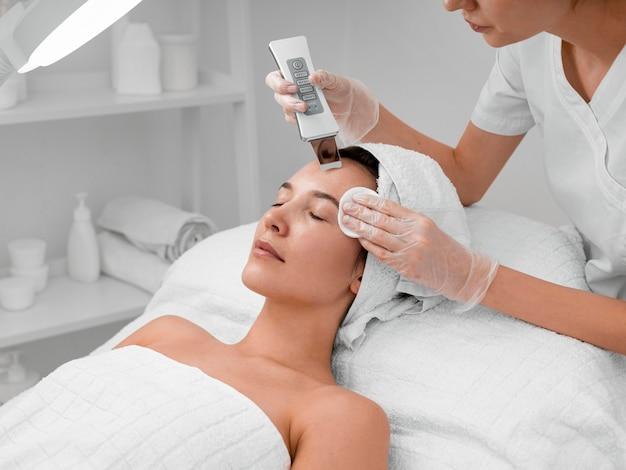 女性のクライアントのための顔の美しさのルーチンを行う美容師