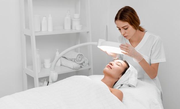 Косметолог делает рутину красоты лица для клиентки