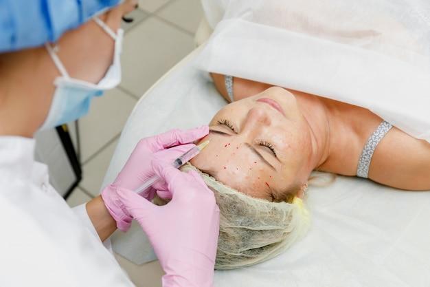 Косметолог делает инъекции лица