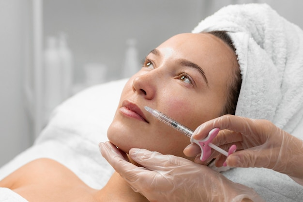Beautician doing filler injection for female client