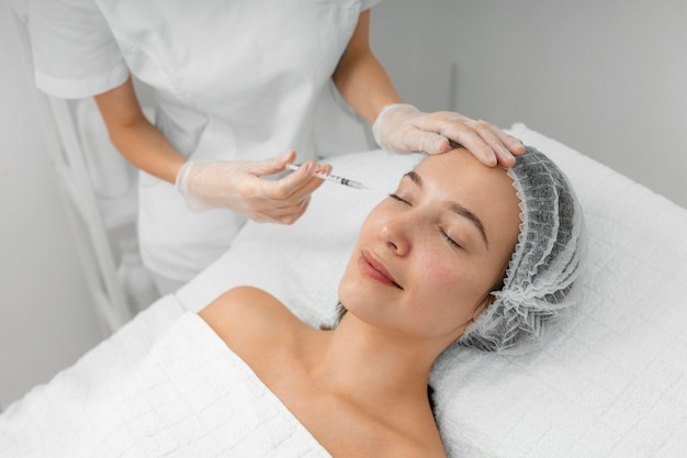 Beautician doing injection filler on female client at salon