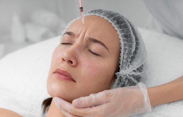Estetista che fa il riempitivo dell'iniezione sul cliente femminile