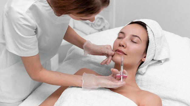 Beautician doing injection filler on female client