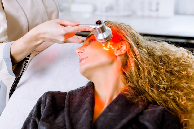 미용사 뷰티 살롱, 피부 모공 클렌징을위한 얼굴 사진 치료에 금발 여자에게 붉은 빛 치료를하고 미용사. 노화 방지 치료 및 사진 회춘 절차를 닫습니다