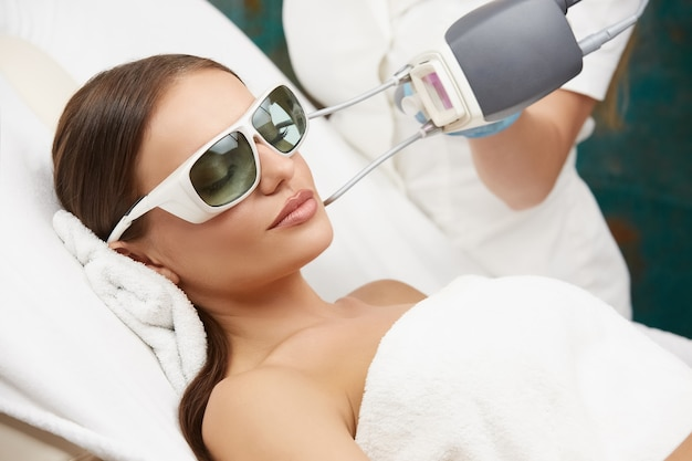Beautician doing removal of vessels on beautiful woman face in luxury spa salon,pretty female receiving facial therapy in beauty salon