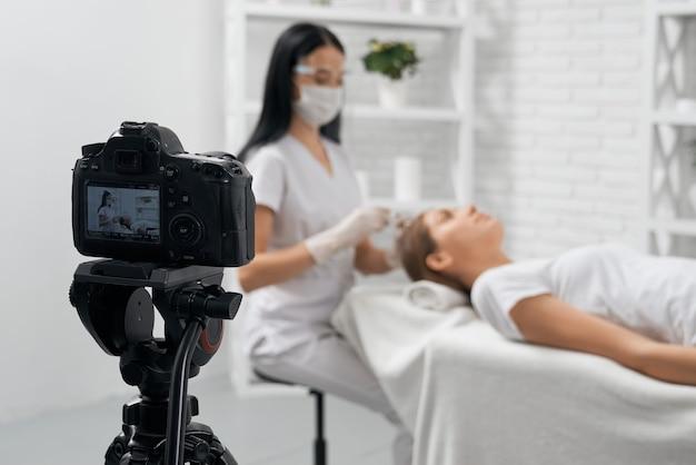 Estetista che fa procedura speciale per capelli sulla macchina fotografica
