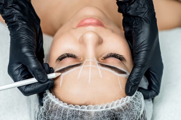 Beautician doing tattooing eyebrow dring permanent make up.